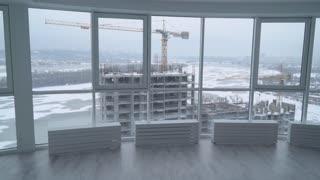 engineer or architect enters into the white modern office real estate company. Businessman working with plan looking on the street with construction house in winter season. man without face wearing in