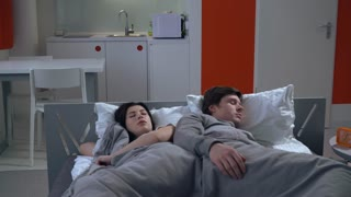 Family lying on bed at seven o'clock in the morning in small apartment. Caucasian girlfriend and boyfriend sleeping at home or hotel