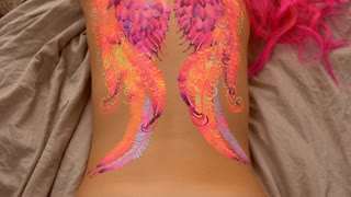 Fascinating artwork on a humans body. Colorful wings on a womans back.