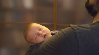 Father holding happy calm baby. Newborn boy sleeping on father's arms