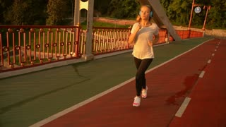 female runner has an active training. attractive lady listening to the music while joggs.