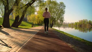 female running in the early morning outdoors. back view woman wearing black leggings and pink hoodie jogging along the river in spring season