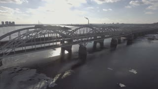 Flying over the railway bridge in the early morning, the sun's rays shine through the bridge, quickly edeut machine. Aeria 4k video