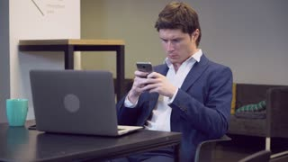 Focused caucasian adult man wearing in elegant suit using smartphone. Businessman chatting with mobile phone texting message or check mail sitting in lobby or in waiting room