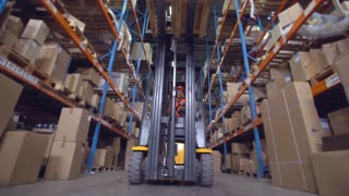 forklift operator puts boxes with goods on the metal racks. worker in storehouse driving on the special vehicle