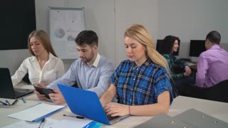 friends watching funny photo their coworker. Young creative people in office talking and laughing sitting at the working place. business team have fun wearing in casual clothes