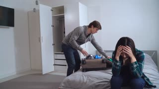 Funny divorce in young family. Caucasian boyfriend or husband packing clothes in suitcase and leave apartment. Young woman happy smiling and celebrating separation