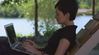 Girl with short haircut and black hair using laptop outdoor. Young woman sitting on the bench in park with lake typing on computer. Lady wearing casual polo shirt working on pc in summer season