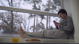 Guy resting in the morning. Man sitting on the windowsill messaging or play game on smartphone using internet at home. Breakfast time in sweet home. Beautiful winter landscape with snow and trees