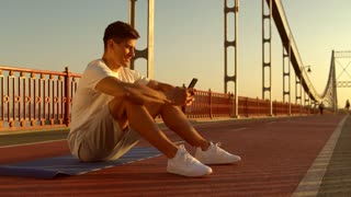 guy sits on the bridge typing a message. caucasian male uses wireless internet.
