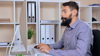 handsome businessman with beard and mustache sitting at the white desk in modern office typing on keyboard. adult worker wearing casual shirt focused on screen computer