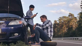 handsome caucasian man changing a tire on the side of the road. Woman using mobile phone messaging or scrolling social media on smartphone