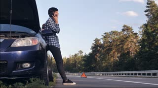 handsome caucasian man changing a tire on the side of the road. Young woman wearing casual clothes has phone conversation on smartphone . Female looking on the guy and smiling