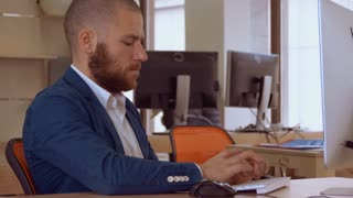 handsome caucasian man with beard sitting at the workspace typing on keyboard looking on screen computer. employee focused at work