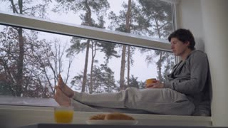 handsome guy drinking coffee or tea holding yellow cup looking outdoors. Wearing in casual hoodie and grey trousers. On the street snowing. Beautiful nature view with trees and pine. Winter in