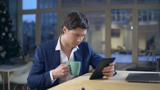 Handsome man wearing in elegant jacket resting reading drinking cup holding touch screen tablet. Caucasian male sitting at the wooden desk in room with big windows