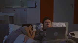 Handsome man working in bed at night. Attractive girlfriend sleeping near him. Young family at home. Woman wearing in t-shirt blanketed. Caucasian man typing on laptop