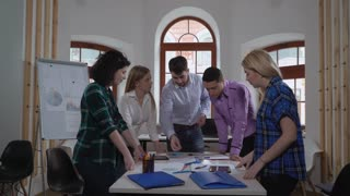 Handsome manager presenting new project to coworkers. Team looking on document with financial data different tables and graphs. Group of young people standing around desk wearing in casual closes