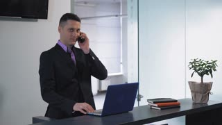 Handsome professional assistant answer call using computer. Adult man talking with client and give information. Employee standing at working place has phone conversation by phone wearing formal suit
