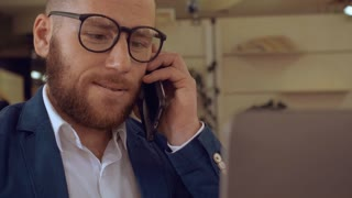 handsome redheaded businesman has phone negotiations in office, successful worker in startup company talking by smartphone with client. bearded manager or entrepreneur smiling during a conversation at