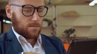 handsome redheaded businesman using touch screen digital tablet indoors. portrait casual man sitting in office of cafe surfing internet reading documents or news. manager wearing white shirt and blue