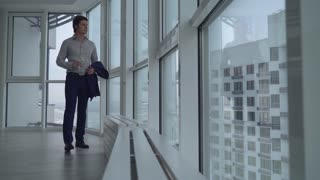 handsome young businessman have a break at work drinking water and looking on the street with urban landscape and high rise buildings. successful employer holding bottle with clear drink and relaxing