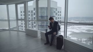 handsome young businessman sitting with suitcase use smartphone typing message. caucasian young professional man leave lobby or waiting room lose cup with coffee