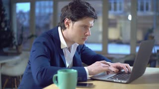 Handsome young businessman working at hard project in startup company. Man computing on laptop in casual office. Guy wearing in elegant blue jacket