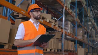 Handsome young employee working at warehouse. Worker wearing high visibility clothing and a hard hat checking and count up goods or boxes for delivery. Man writing some notes