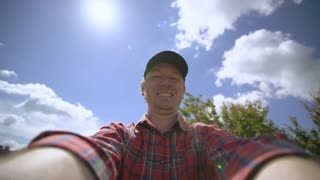 Happy adult caucasian man take a selfie photo outdoors. Portrait men wearing in cap and bright casual shirt in sunny day. Green summer nature view and blue sky in garden