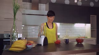 Happy adult woman making fruit smoothie with strawberry. Caucasian brunette standing near table with blender in the kitchen at home