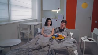Happy couple enjoy breakfast in bed. Smiling young man and woman talking laughing drinking coffee in small modern apartment