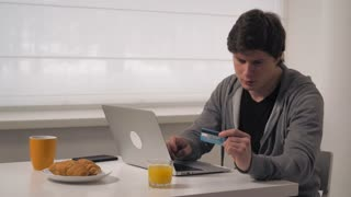 Happy man shopping online sitting at the table with breakfast food and orange juice. Guy using laptop and internet for shopping online in house