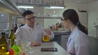 happy scientist teaching young assistant or student how conduct an experiment. Woman and man discussing results