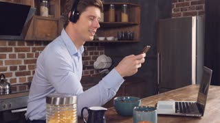 Happy smiling businessman listening new song using headphones. Cheerful man enjoy breakfast and favorite playlist in the kitchen at home. Caucasian model wearing casual clothes holding smartphone