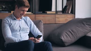 Happy smiling man sitting on the couch using smartphone in living room. Young muscular guy messaging or sharing in social media