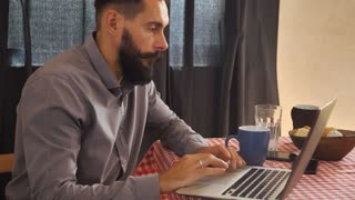 hipster man using laptop. Handsome guy with beard and mustache sitting at the table at home. Attractive trendy businessman working in apartment