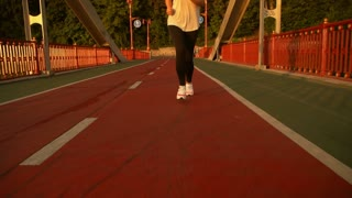 lady joggs alons the bridge. female runner wearing black and white outfit.
