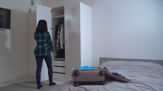 Lady try on dress and put it in suitcase. Young woman wearing in casual clothes packing bag planning vocation. Caucasian girl with black hair in apartment
