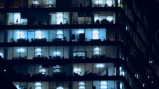Large windows of the office building in the evening, office staff are walking around the office. Time lapse