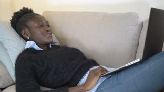 Laughing afro american woman watching comedy at home. Smiling girl lies on sofa using laptop enjoy new season television show