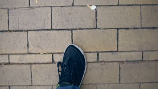 man is walking on the pavement. top view of the feet in black footwear.