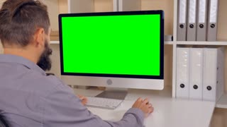 man sitting at workplace paying game on computer in small office. businessman with beard looking on display with green screen. employee in startup company typing on keyboard use pc mouse