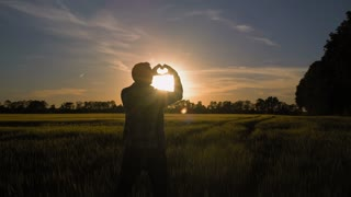 Man standing at the field showing heart symbol at sunset. Male rear back view at sundown nature landscape with setting sun in evening sky