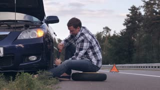 Man stuck on the side of the road with a flat tire. Caucasian driver change a tire at the roadside