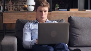 Man working with computer in studio apartment. Young businessman using wifi typing on laptop at home