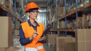 Manager female working at warehouse. Attractive young woman worker wearing uniform hard hat and orange vest, counting box for delivery filling up form holding pen