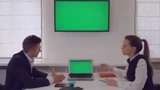 Manager giving presentation for client showing on monitor with green screen. Middle aged businesswoman wearing in elegant black dress. Two people has meeting in modern office