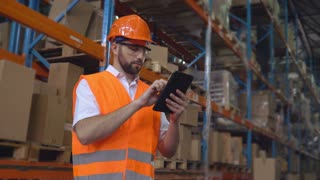 Manager in delivery company standing near metal racks with parcels in cardboard boxes. Handsome mixed race man using digital tablet. Employee in warehouse considering logistics