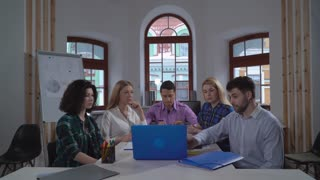 Manager telling about new project coworkers focused on speaker and computer screen. Young team at the meeting boardroom startup company. Handsome men and attractive caucasian women listening carefully